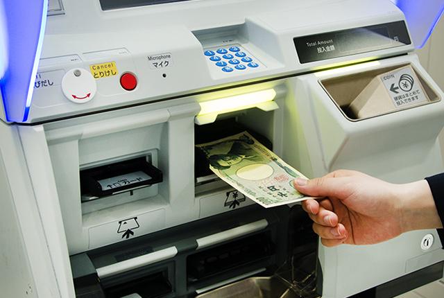 inserting money to buy pasmo